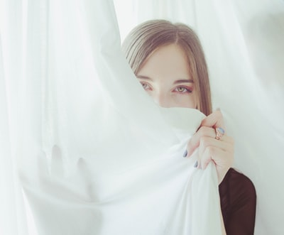 woman hiding on cloth sheet teams background