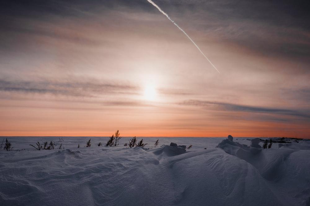sunlight through clouds over snow field