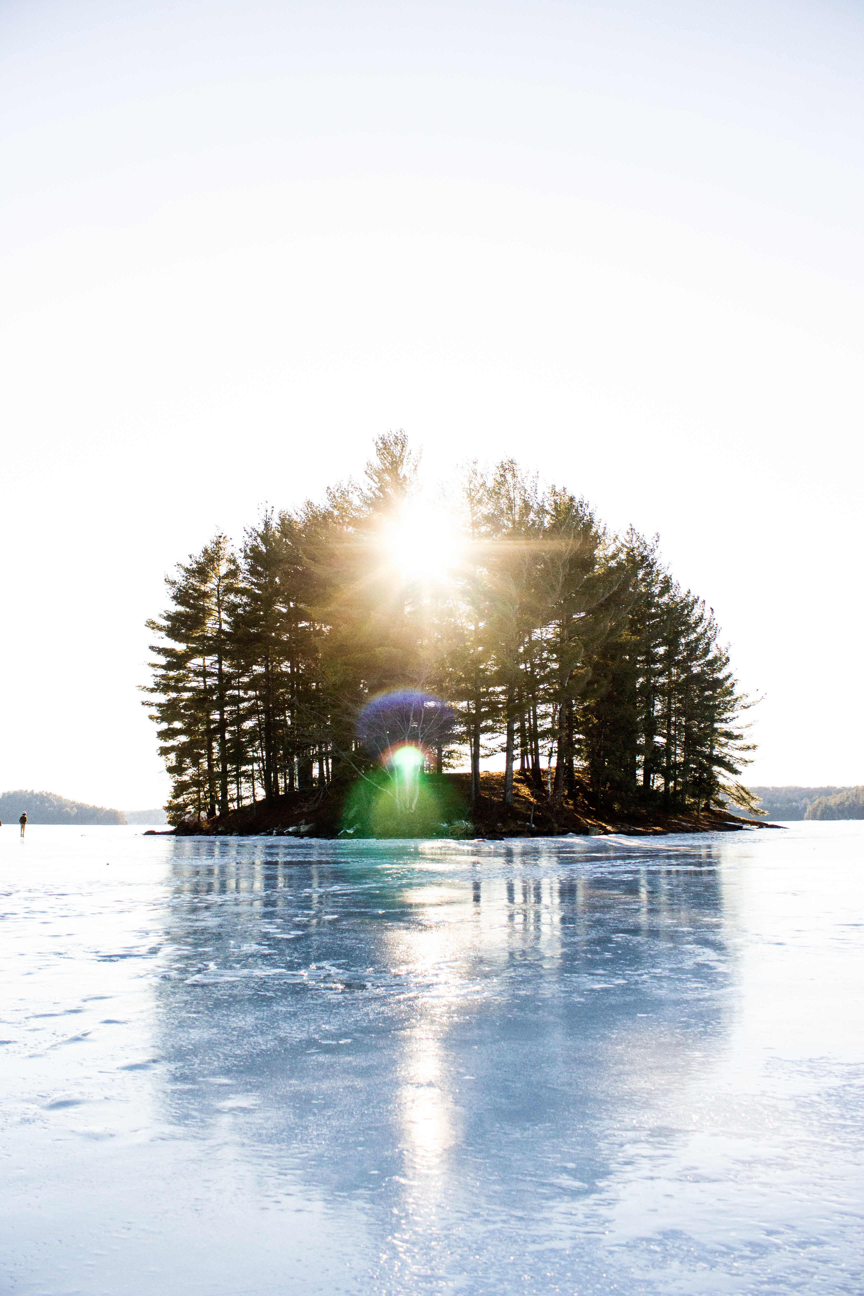 This is an island called Dead Man's Island located on Mary Lake in Huntsville, Ontario. The ice was thick enough to walk on, so one of my photographer friends and I decided to venture out onto it. On the way there, the wind was so strong it actually pushed us a little bit to the side on the icy lake. Once we reached the island we were stunned by the Canadian winter beauty. Whenever I look at this photo I imagine this island being the crown of the lake and the sun being the glimmering jewel on the crown. It certainly seems to have a royalty about it.