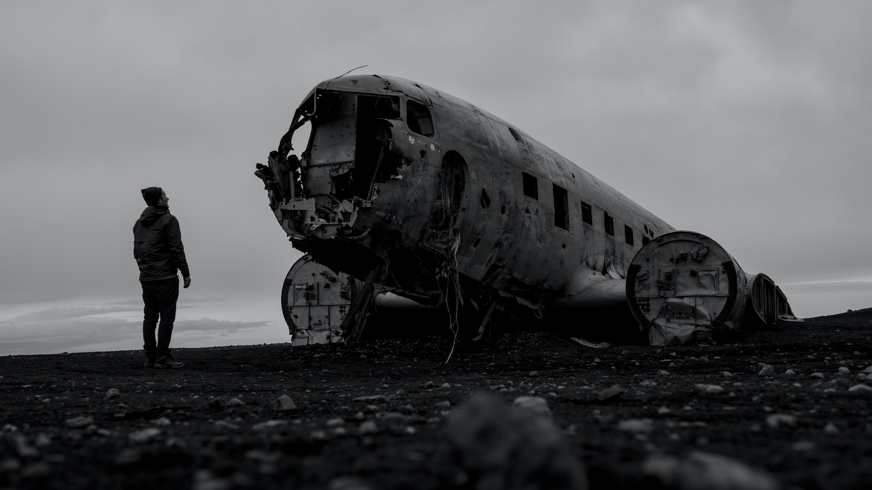 man standing beside crashed plane