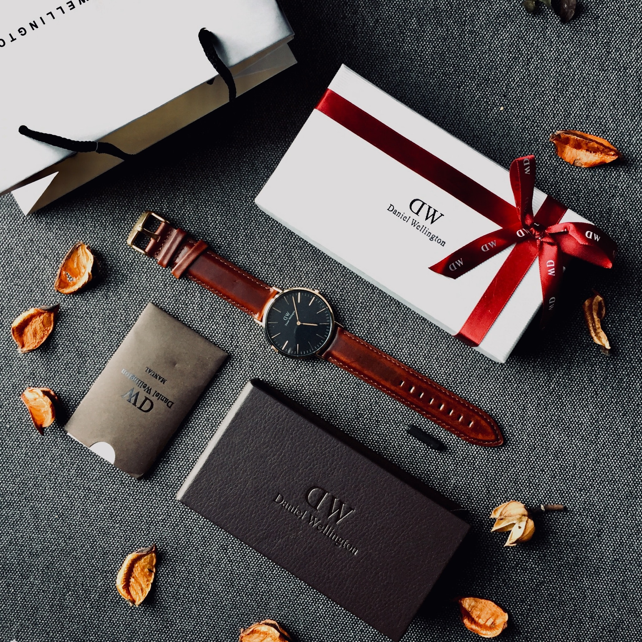 round black analog watch with brown leather stral with box and paper tote bag on gray yextile