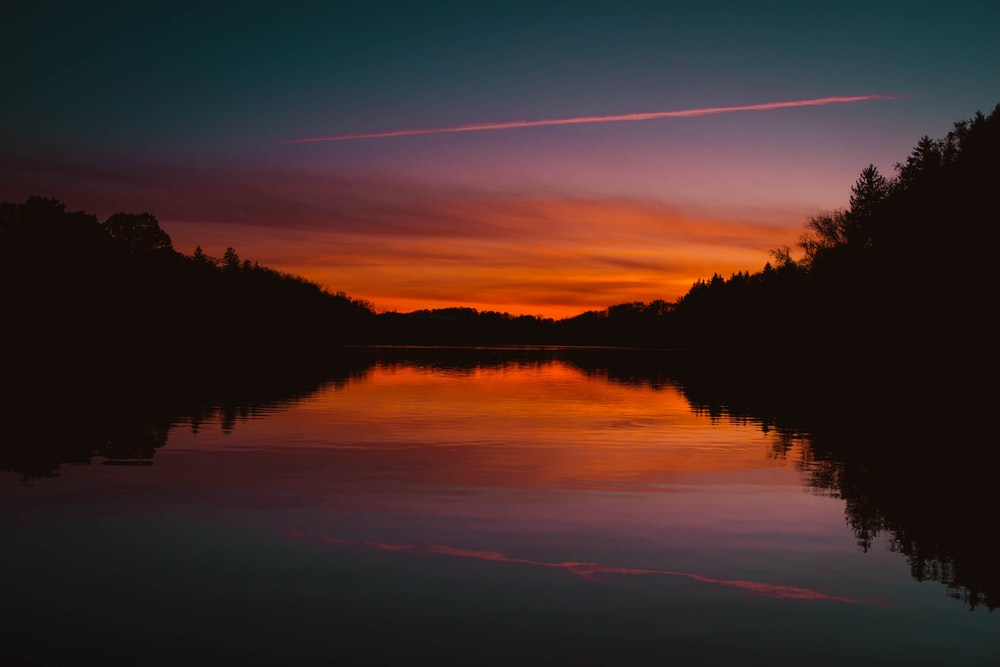 red sky reflecting body of water