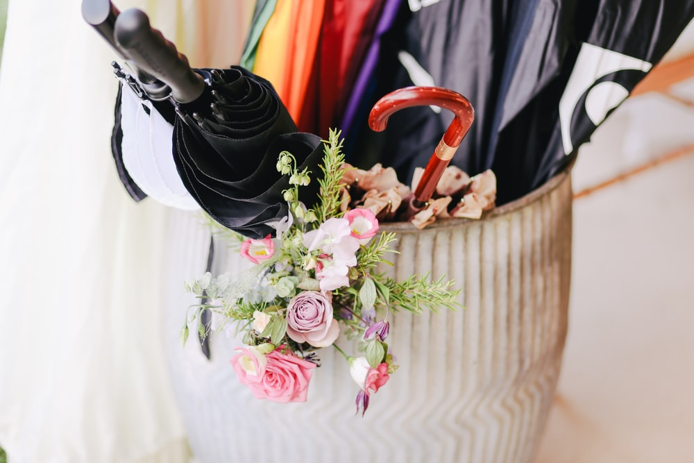 umbrellas inside white clay floor vase with pink petaled flowers in closeup shot