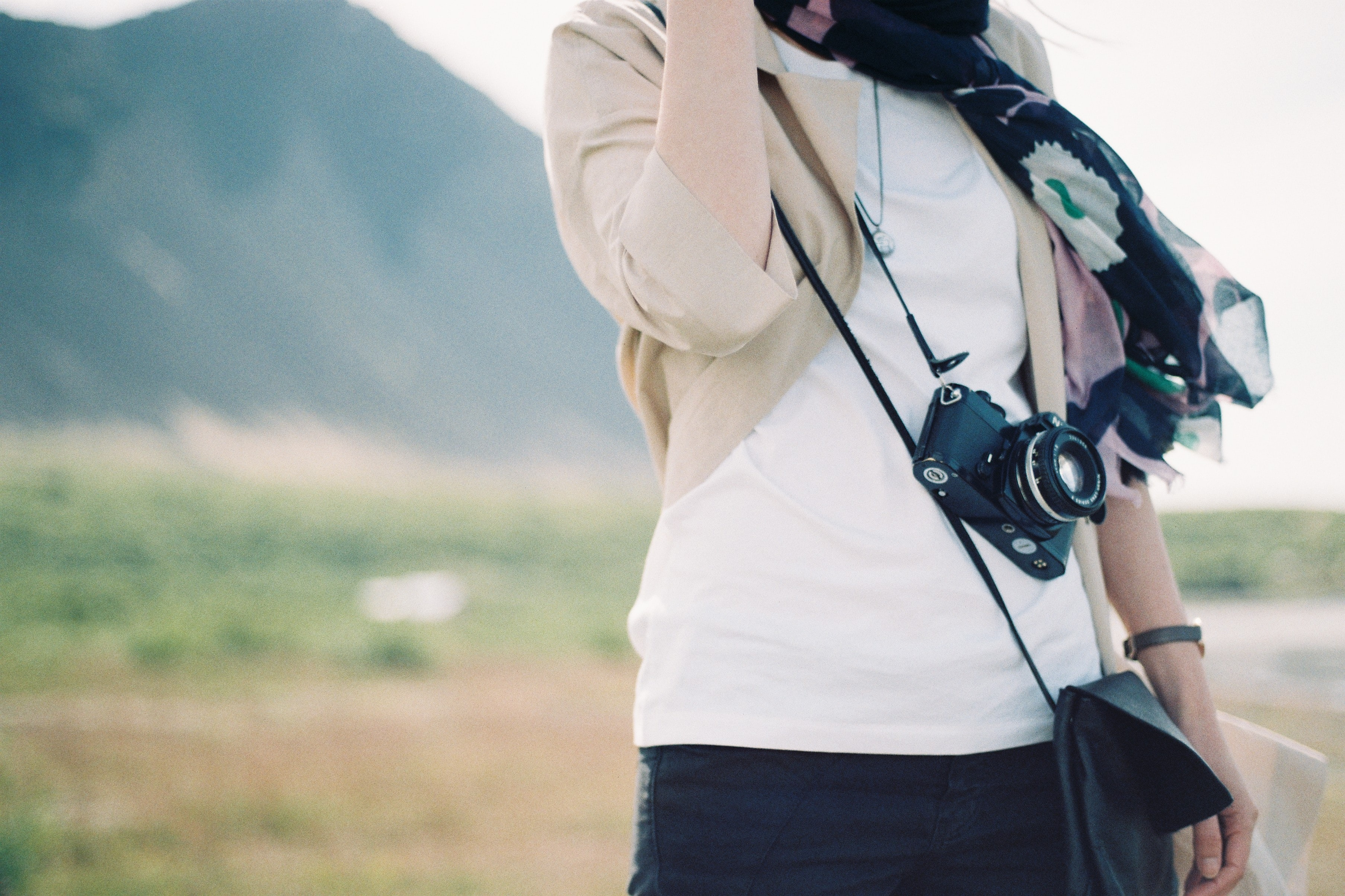 person carrying a black DSLR camera