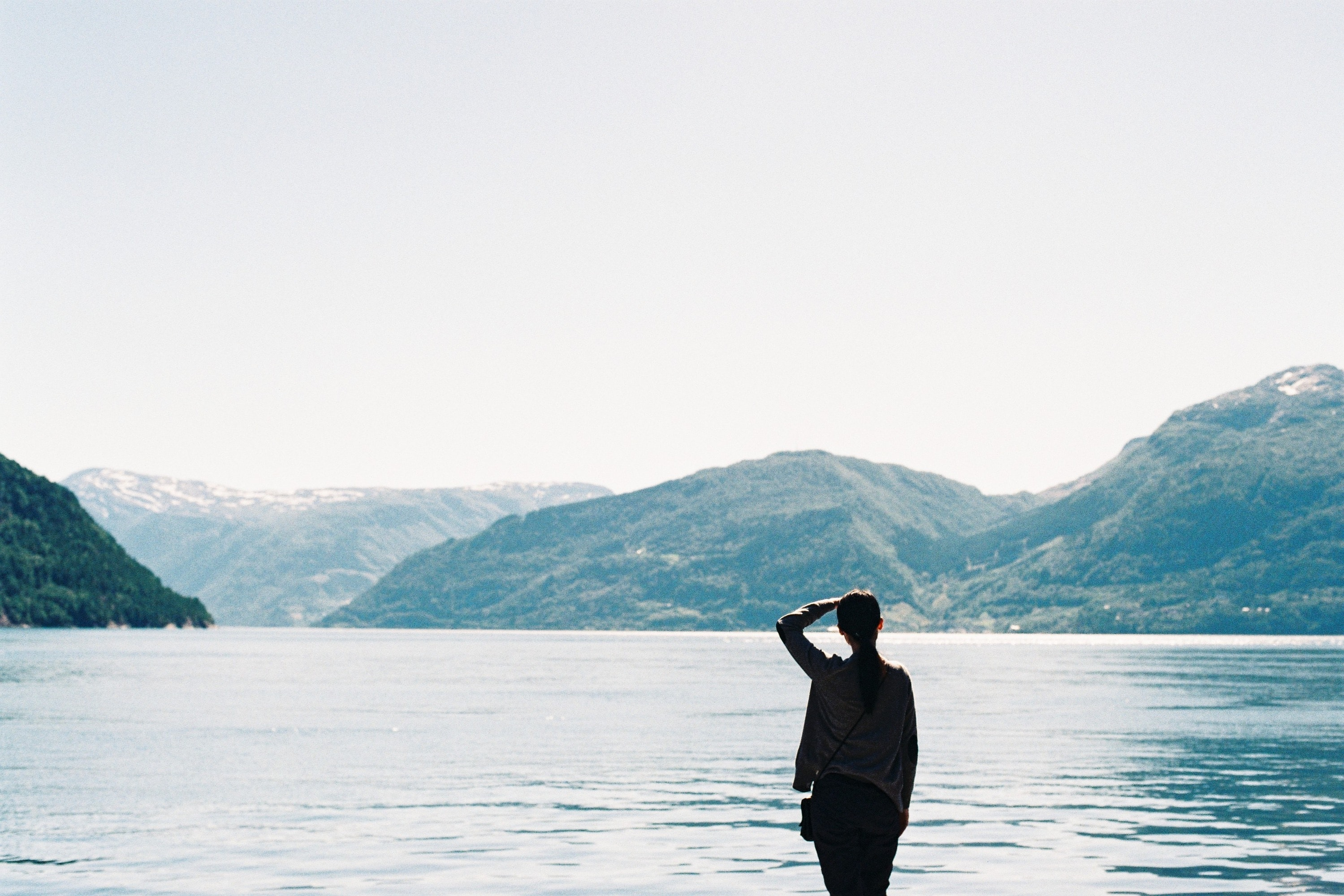 silhouette of person near body of water and mountains at daytime