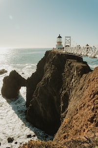 white lighthouse above hill surrounded by ocean during daytime