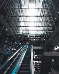 black escalator inside glass building
