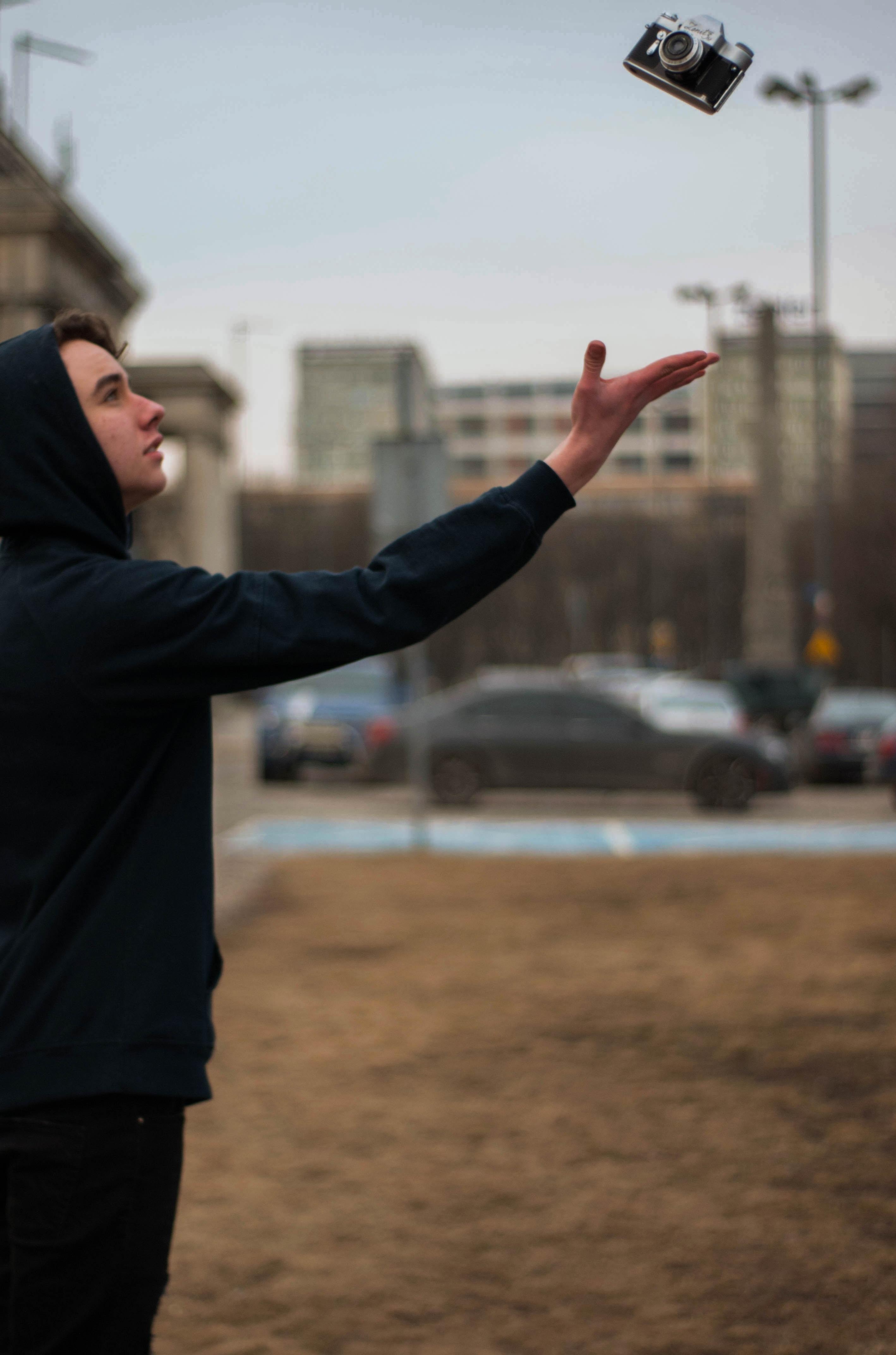 selective focus photography of man reaching for black bridge camera