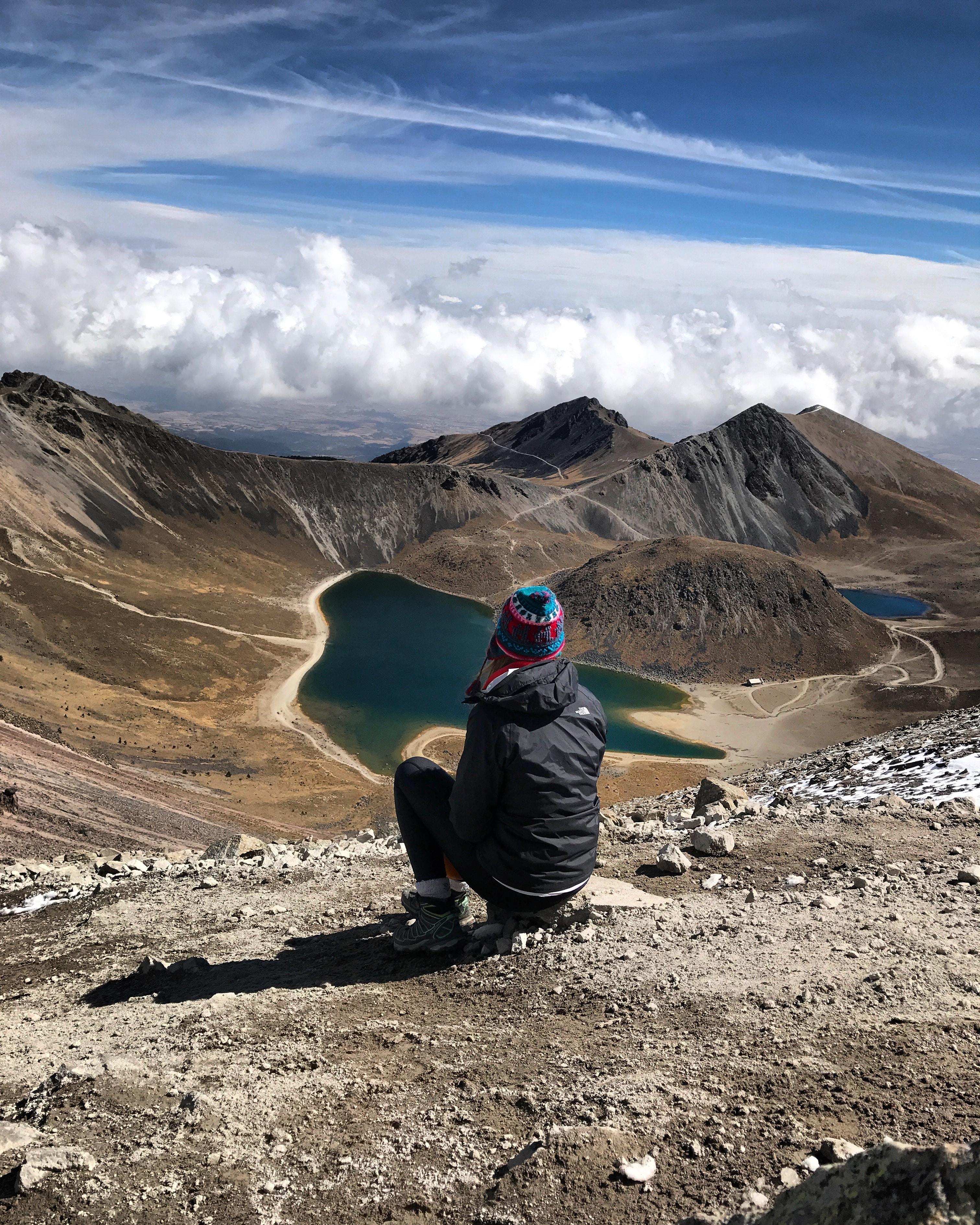 person sitting on stone on mountain