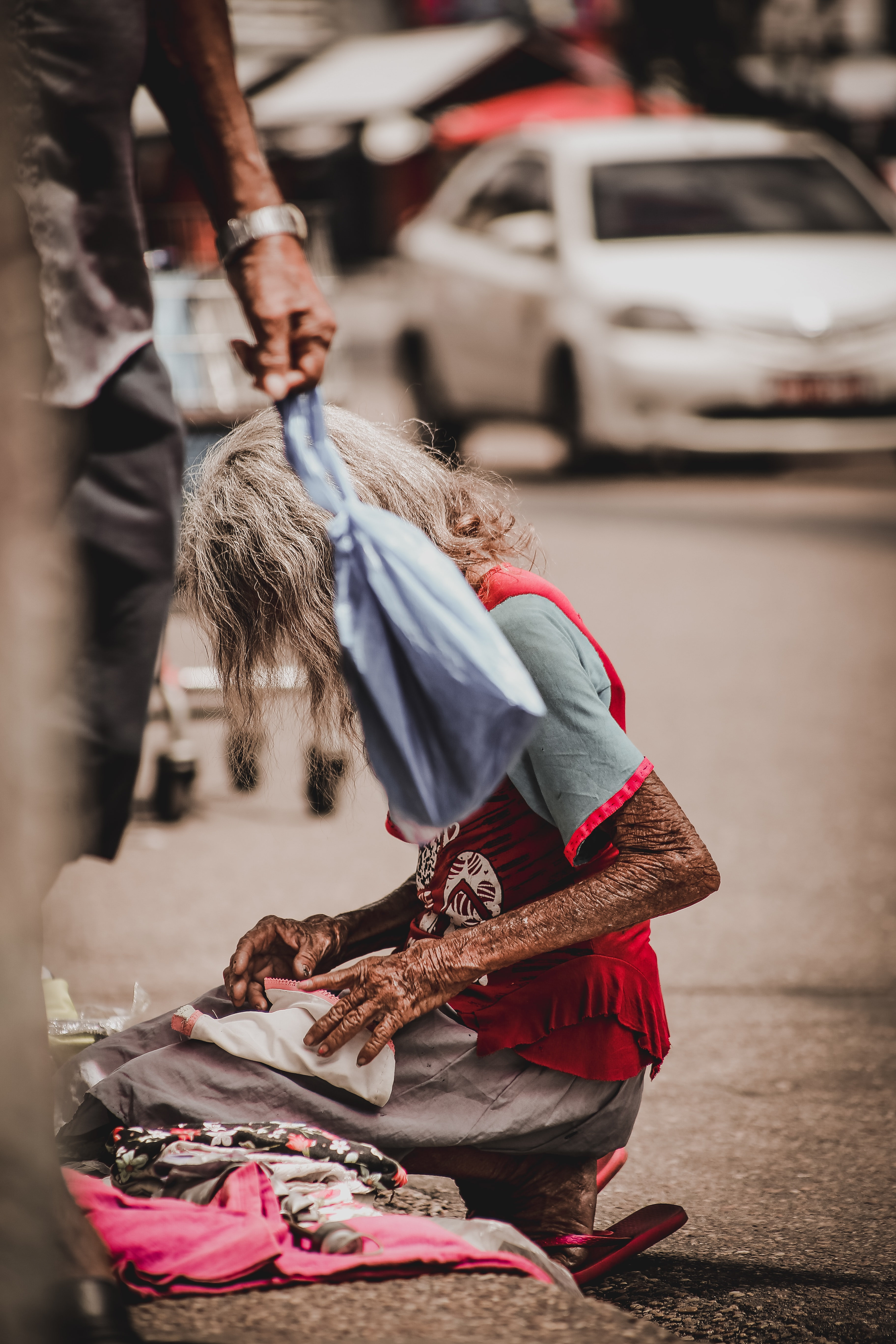 old woman kneeling on road