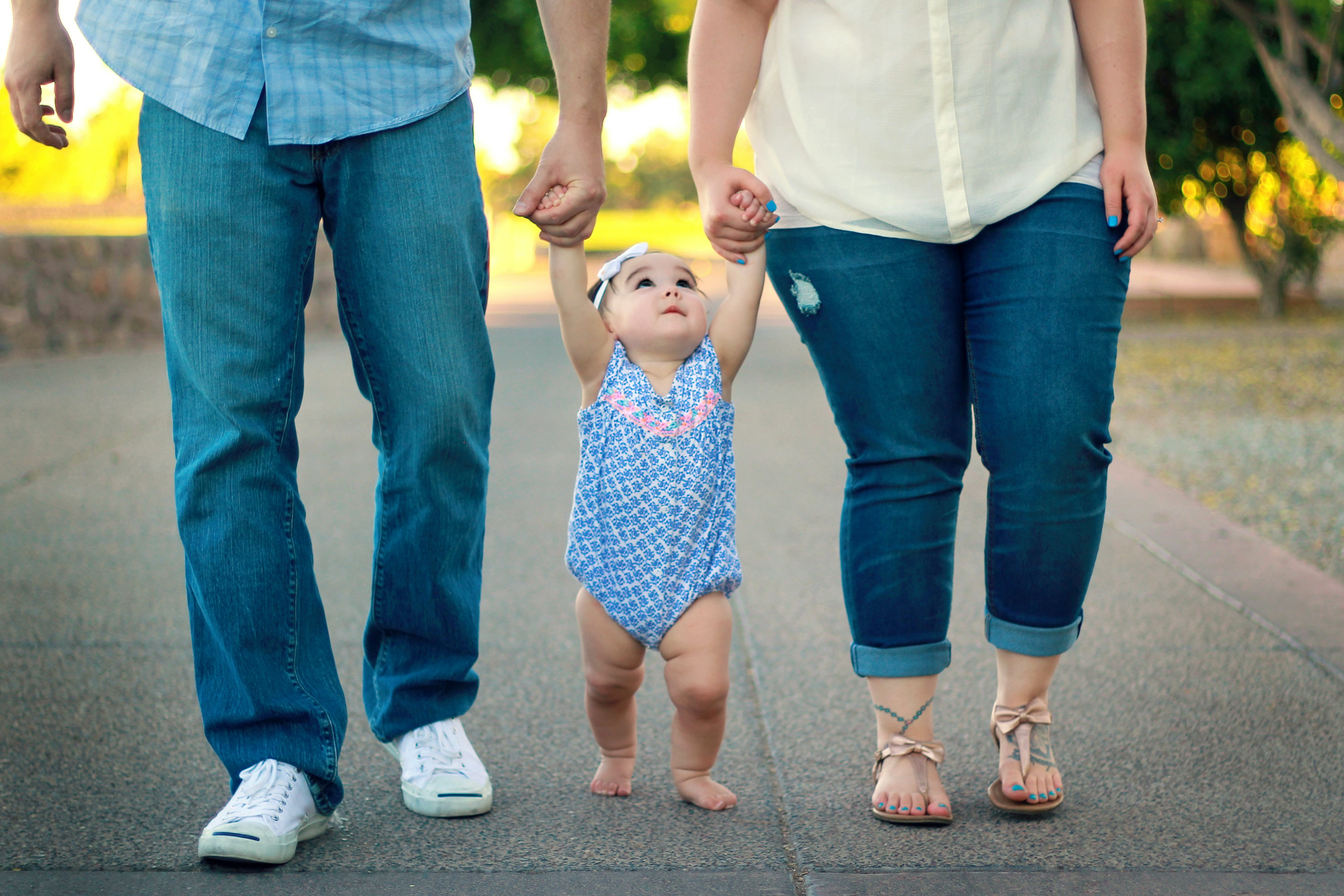 man and woman holding baby's hand while walking on road