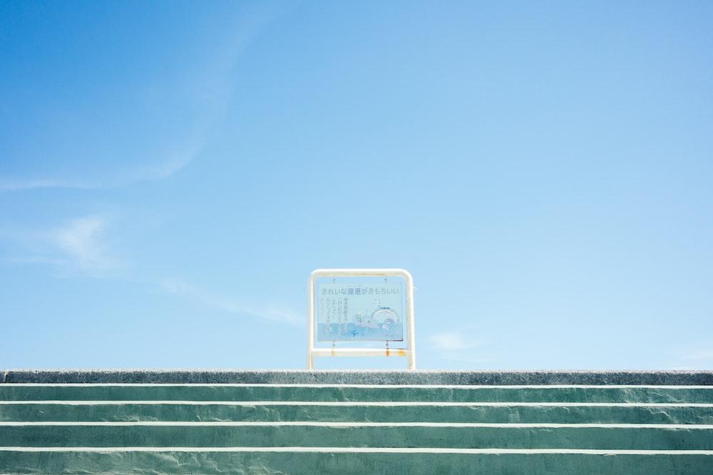white metal framed board on stairway under blue sky
