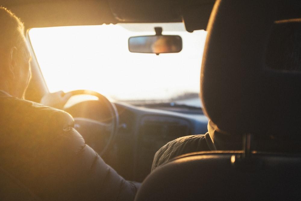 man driving car during golden hour