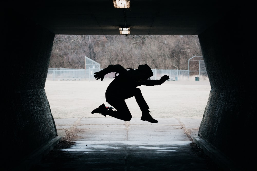 silhouette of man jumping in tunnel