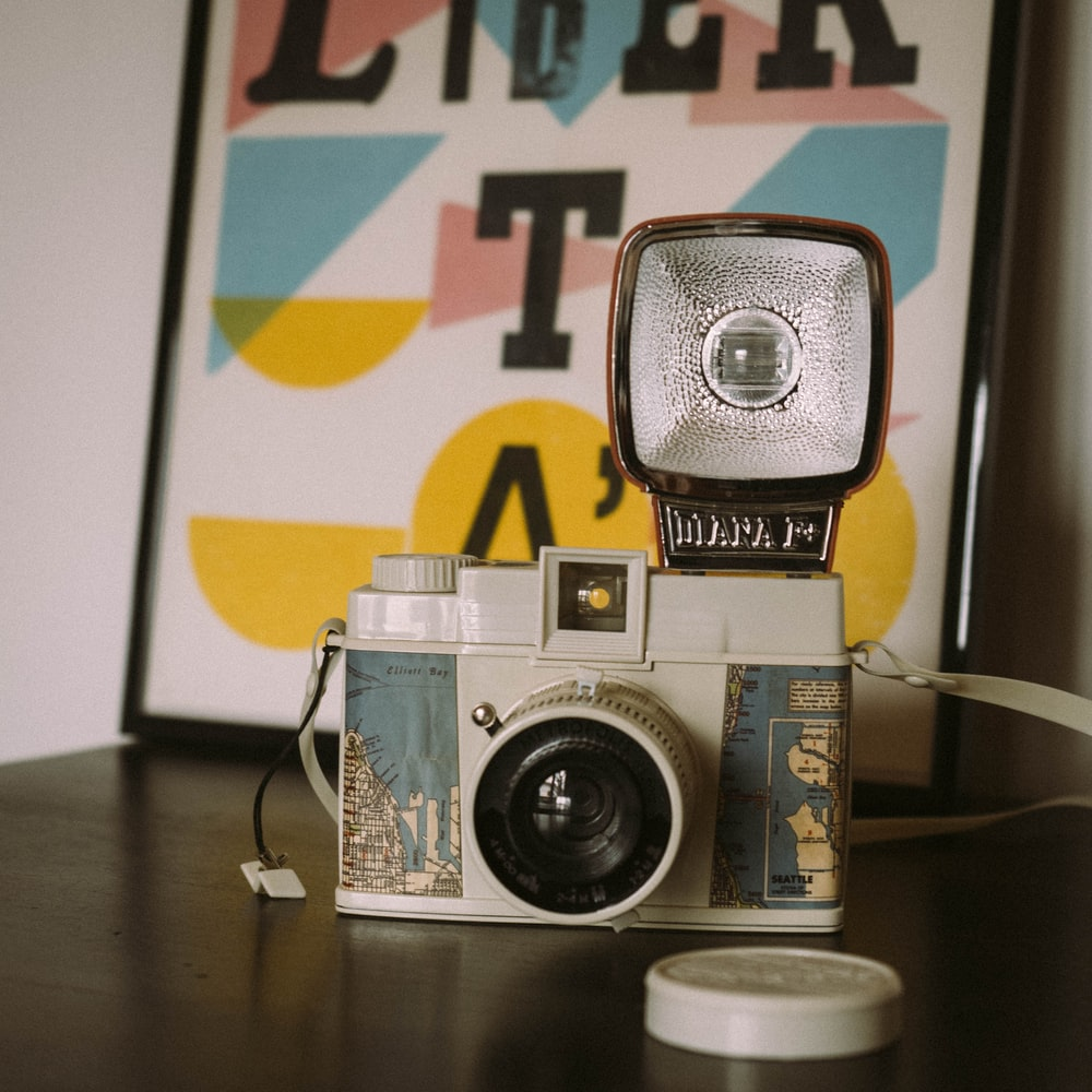 white and green camera on table