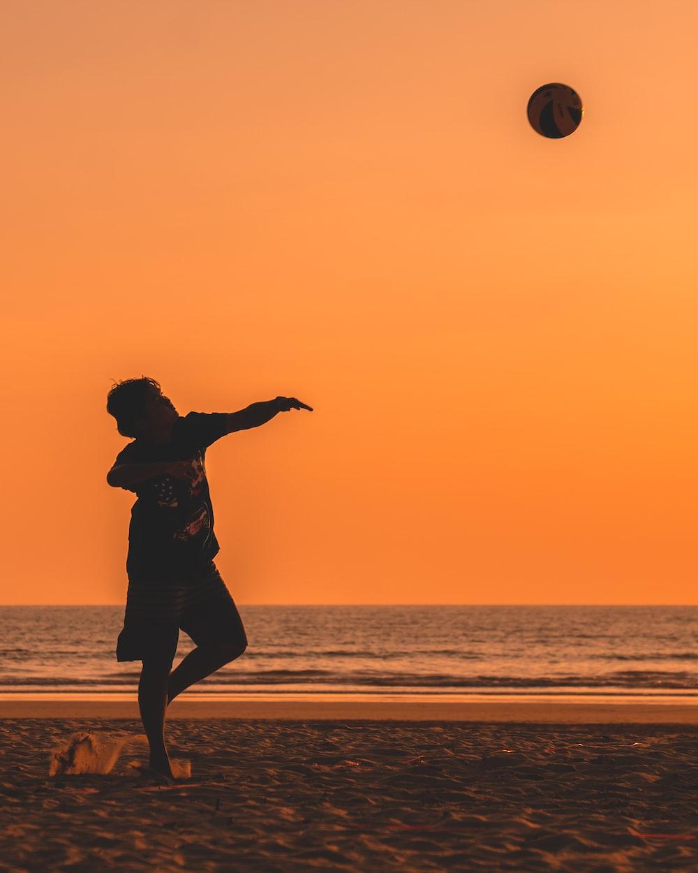 silhouette of man throwing ball near ocean at golden hour