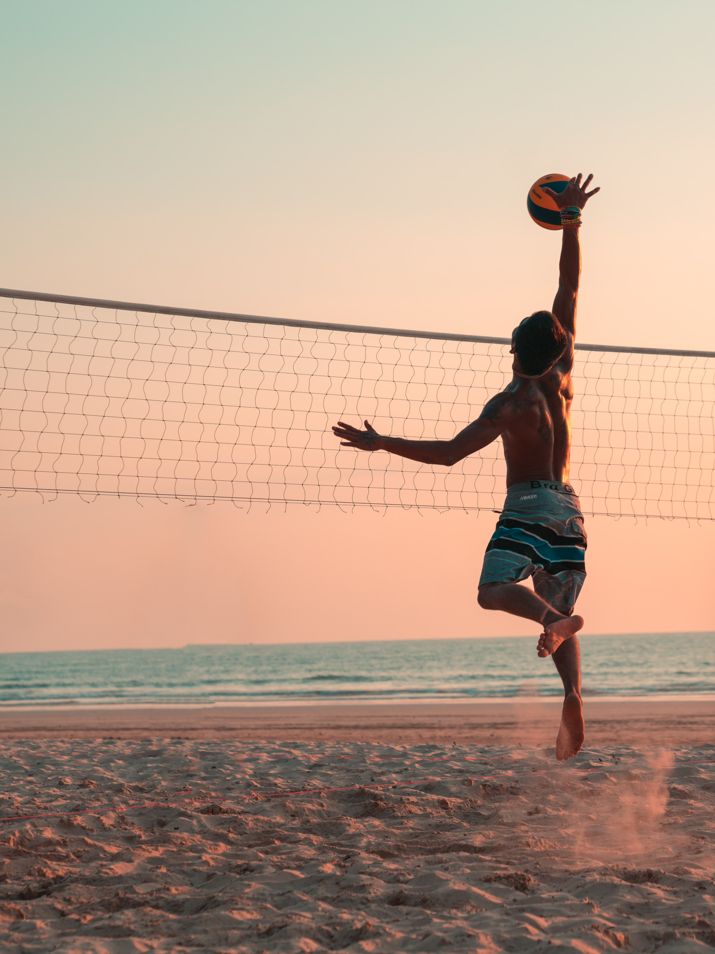 man playing beach volleyball during daytime