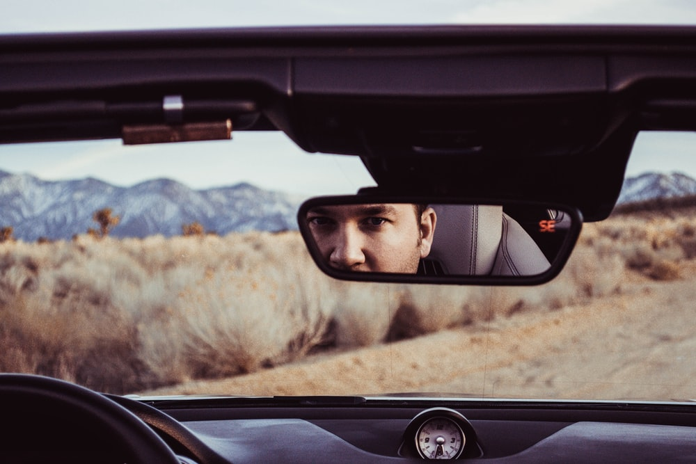 person staring at rear view mirror