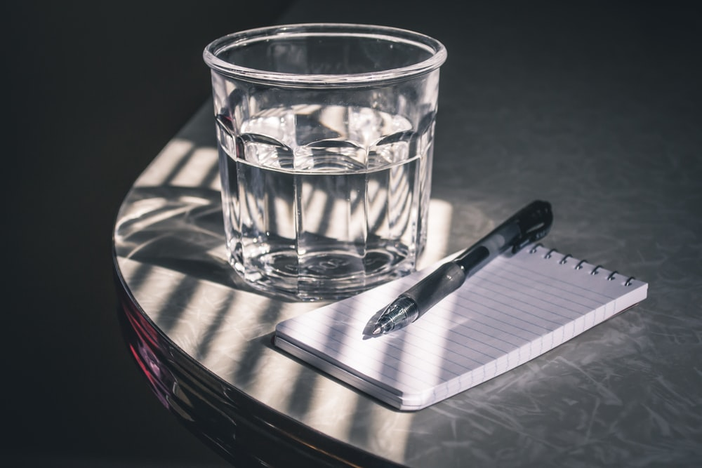 clear drinking glass beside pen and paper