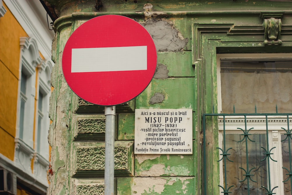red and white road signage near green concrete structure