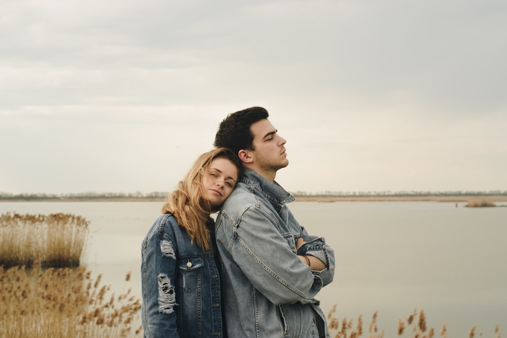 woman in blue denim jacket leaning on man's shoulder near body of water