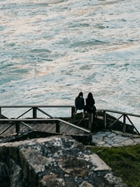 two woman sitting on bridge baluster