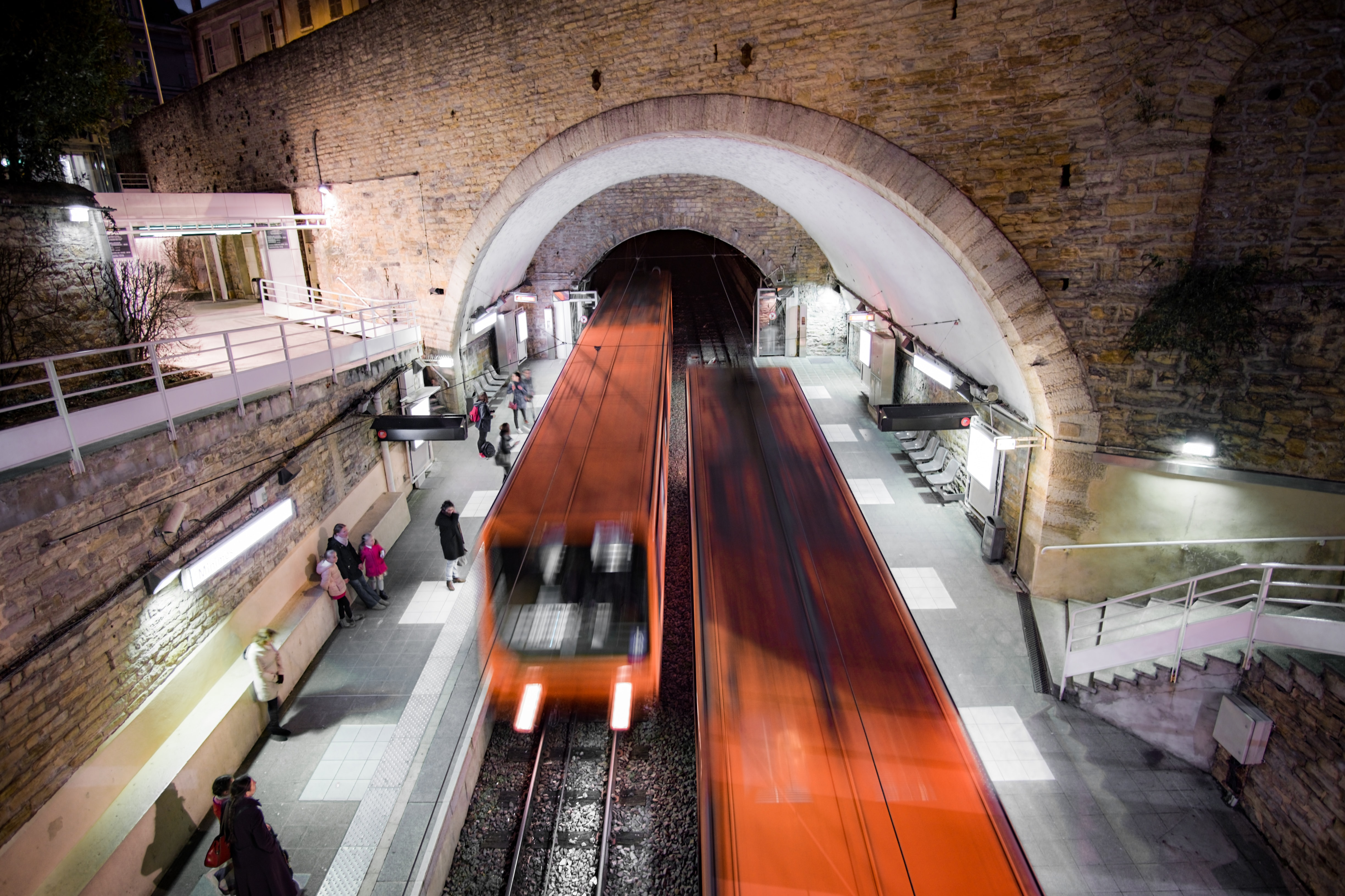time lapse photography of subway trains passing from and through tunnel