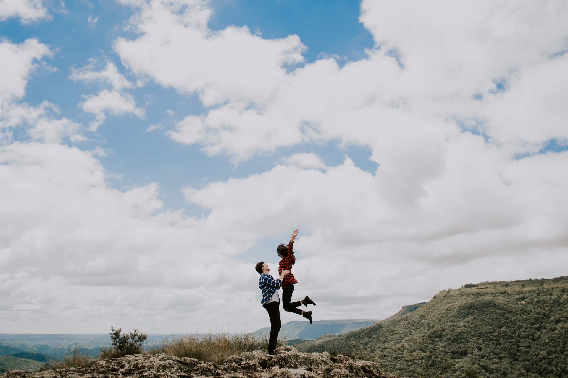 man lifting woman on top of the mountain
