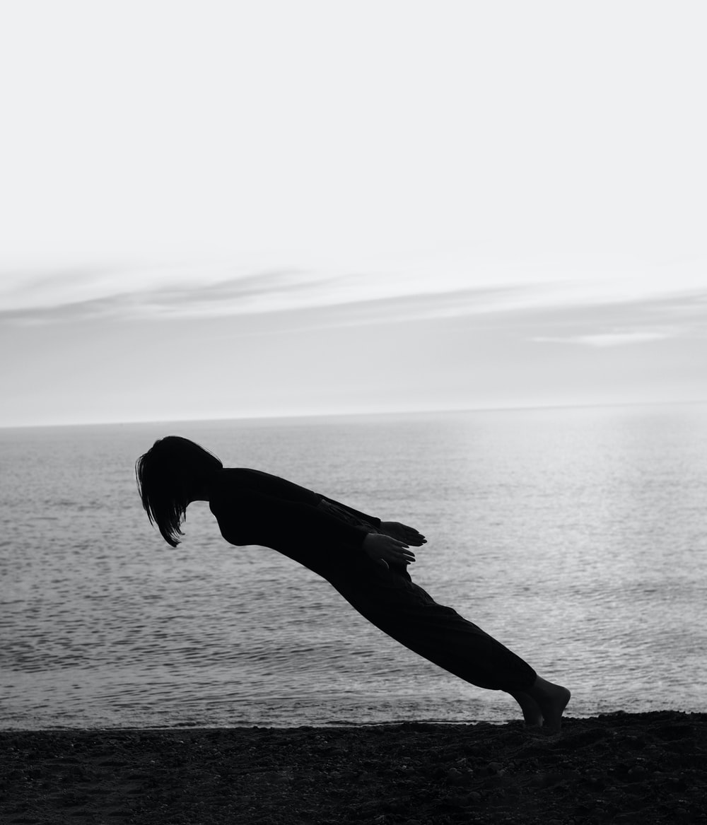 person doing gravity lean on the shore