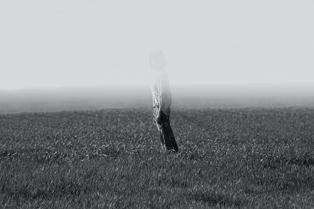 grayscale photo of person standing on field
