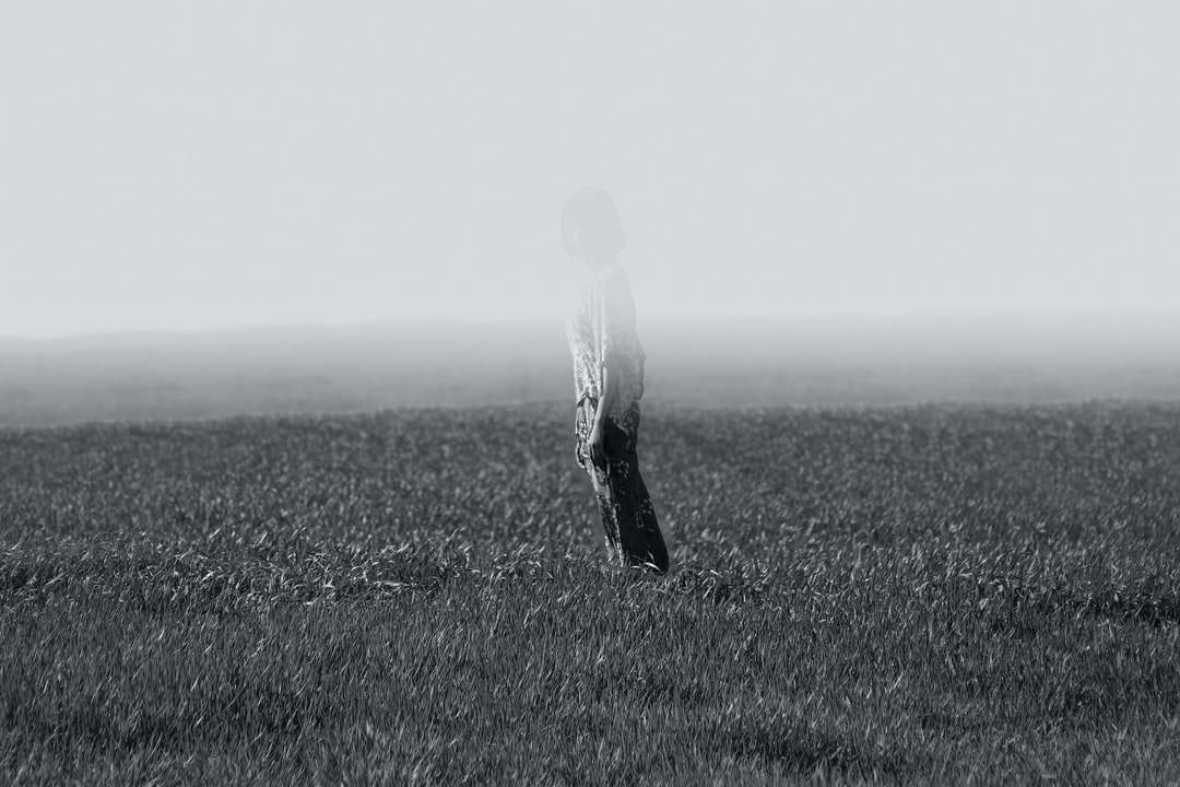 Grayscale Photo Of Person Standing On Field Photo  Free -8965