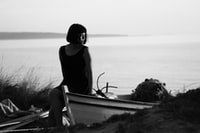 grayscale photo of woman sitting on boat while looking at the sea