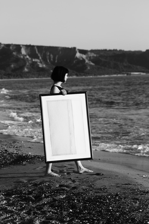 grayscale photo of woman walking on seashore white holding rectangular wooden photo frame