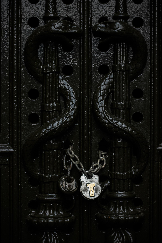 gray chain padlock on door in closeup shot