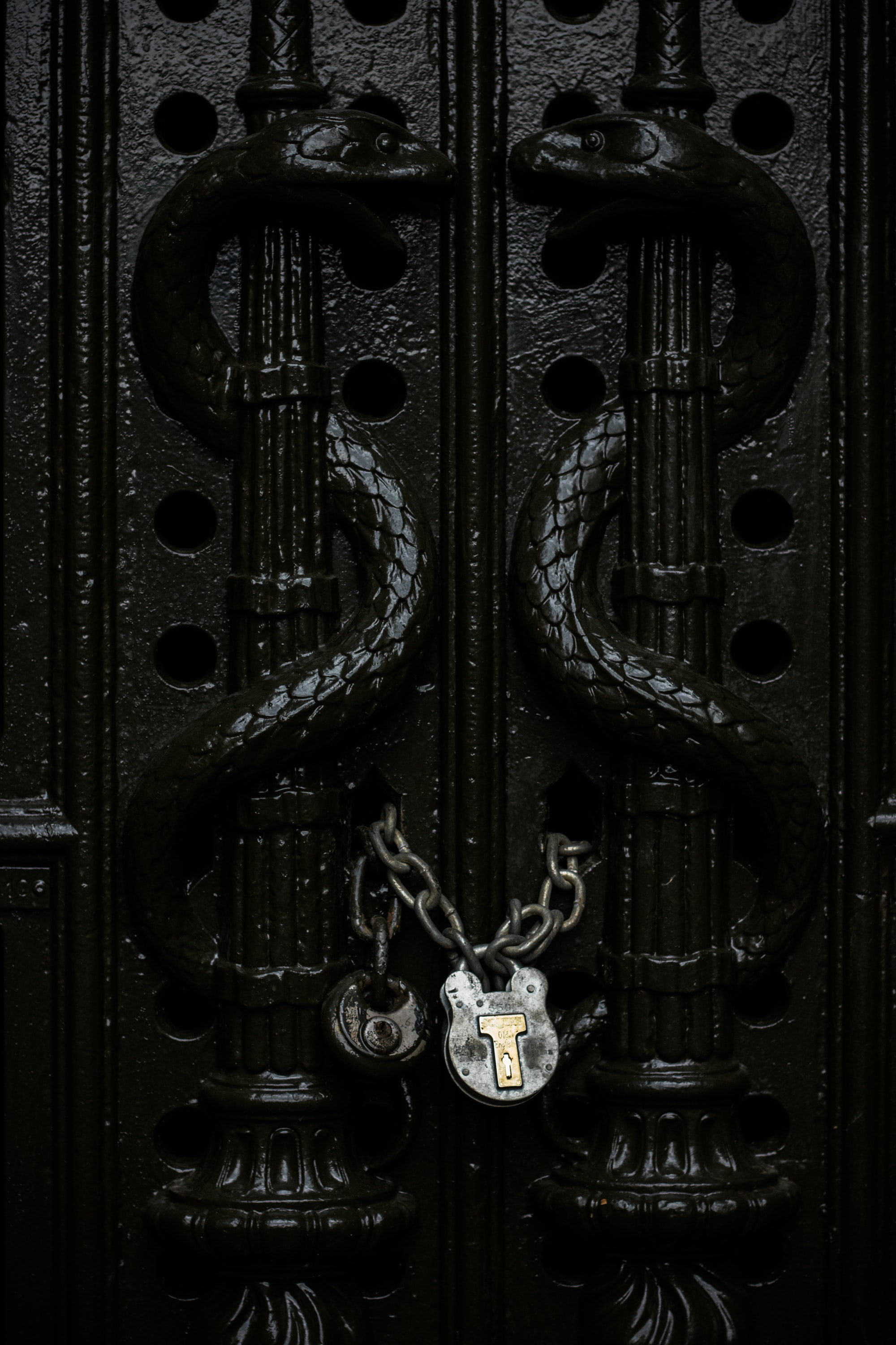 gray chain padlock on door in closeup shot