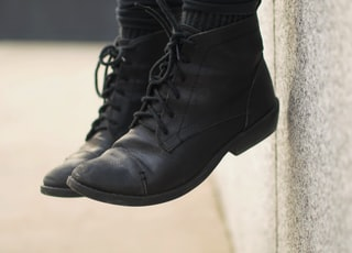 person wearing black lace-up boots