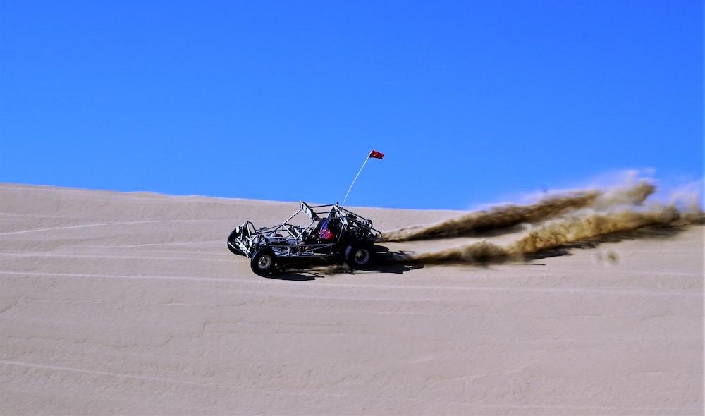 black and blue dune buggy driving on desert