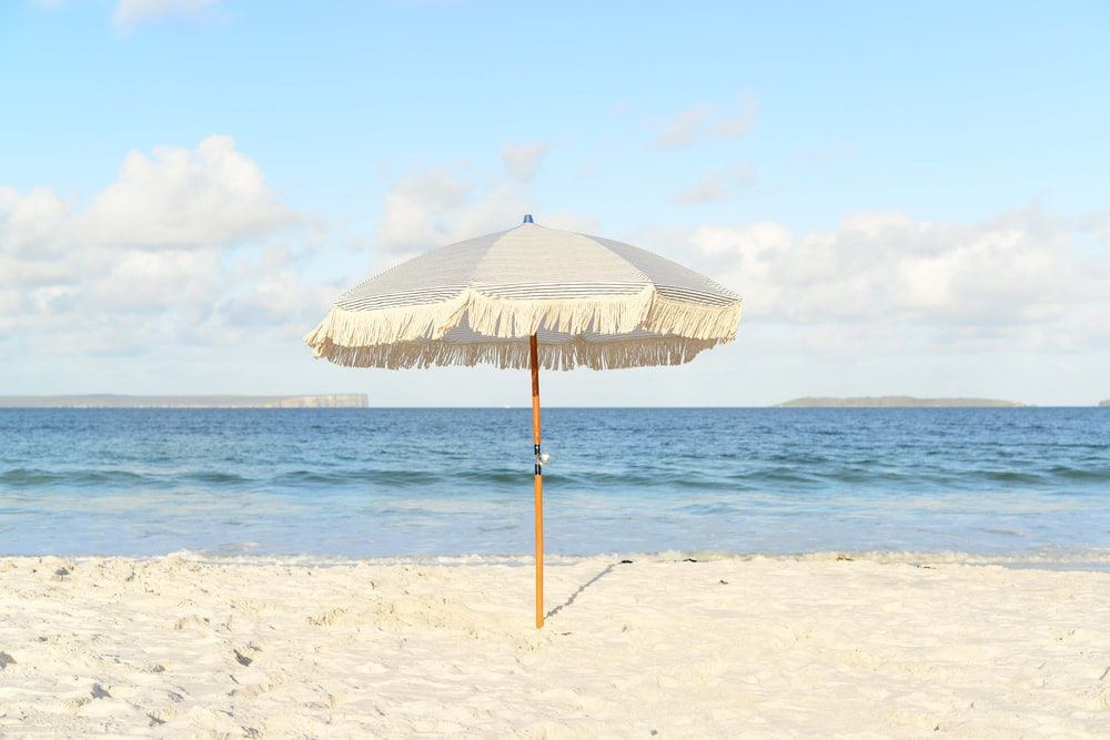 white umbrella on seashore