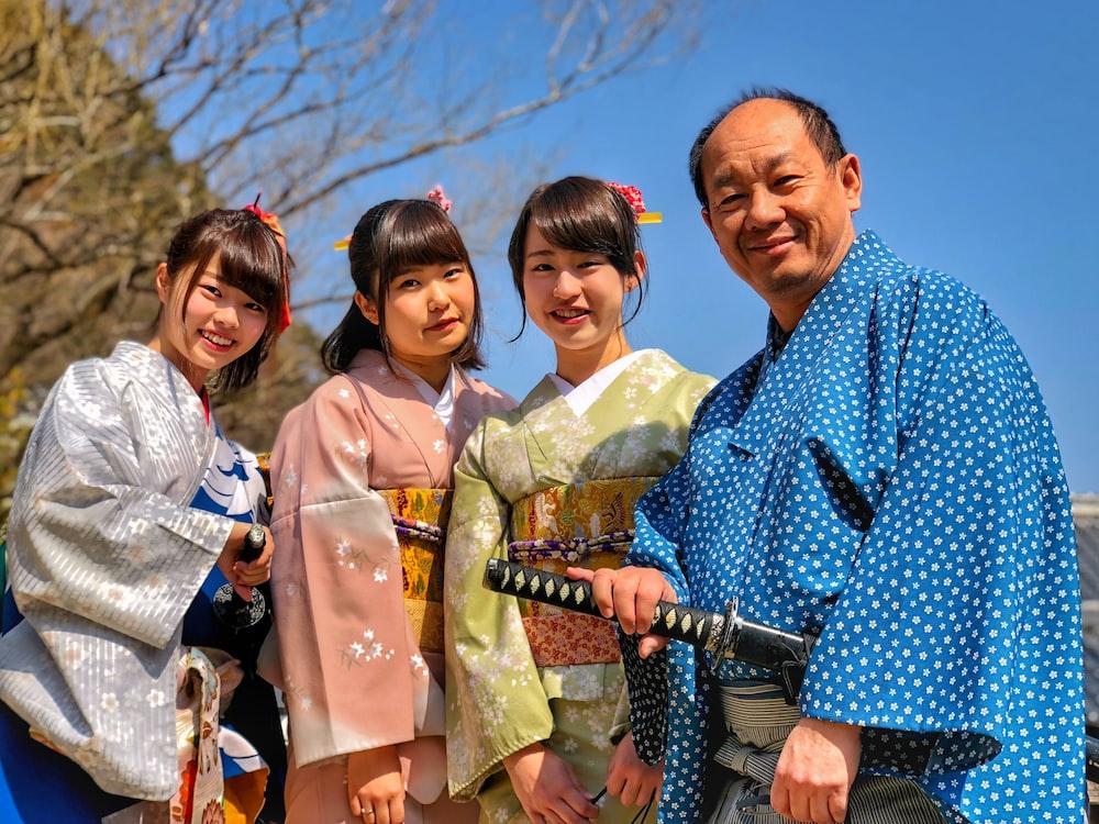three women wearing kimono beside man holding katana sword