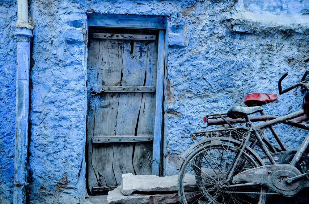 two bicycles beside blue concrete structure