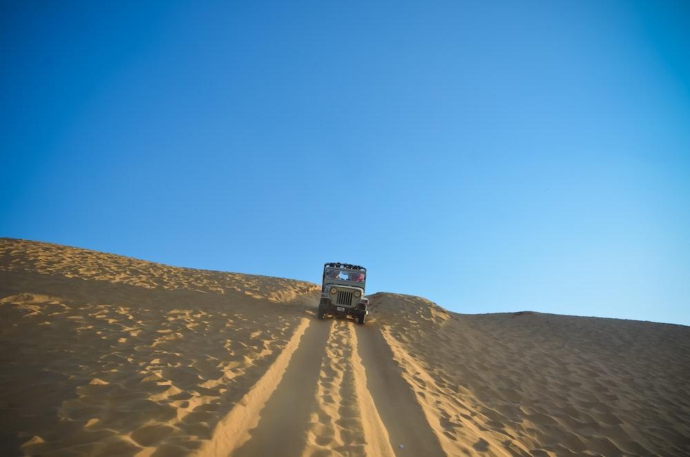 white car travelling on desert