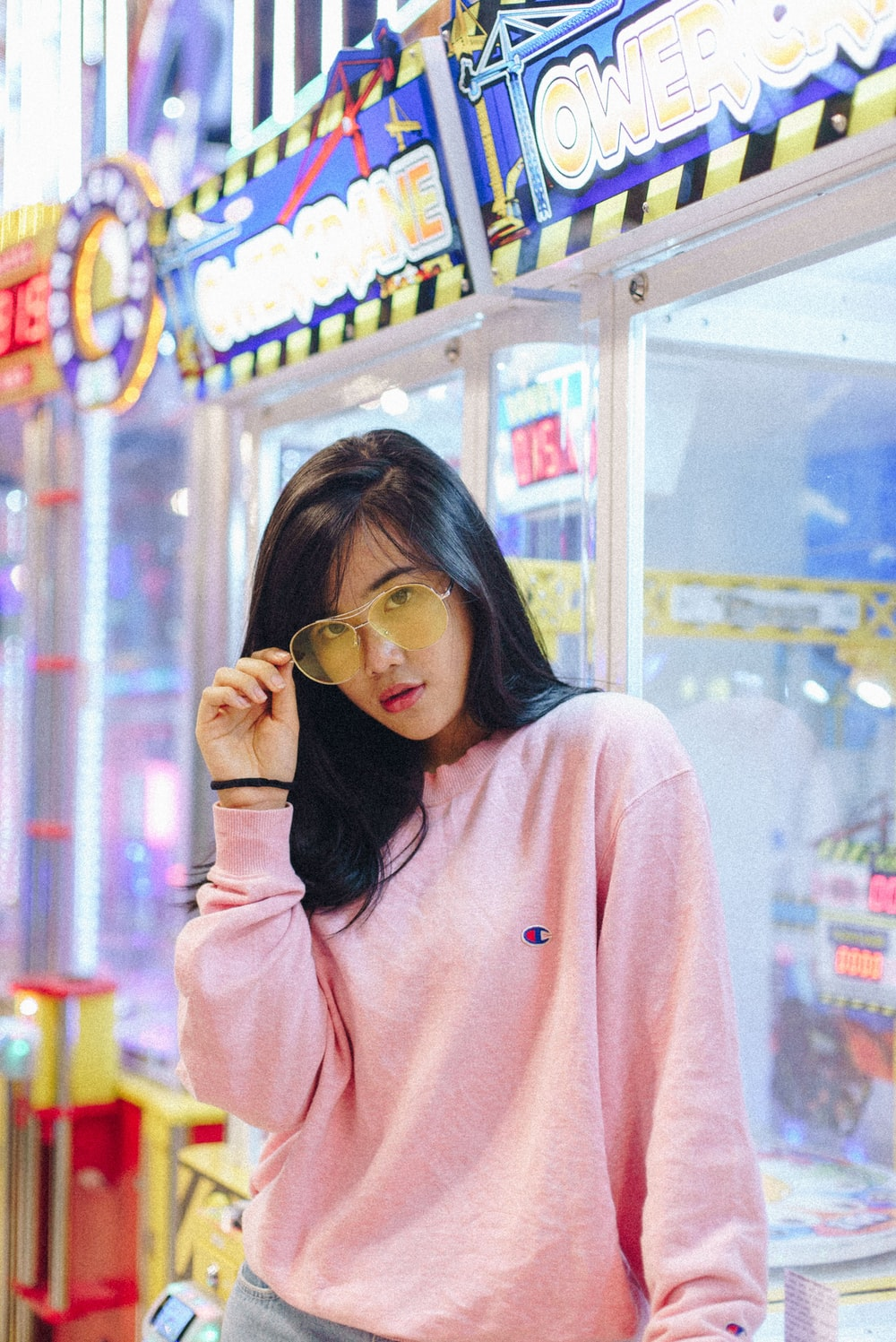 woman in pink Champion sweatshirt holding her sunglasses leaning on game machine