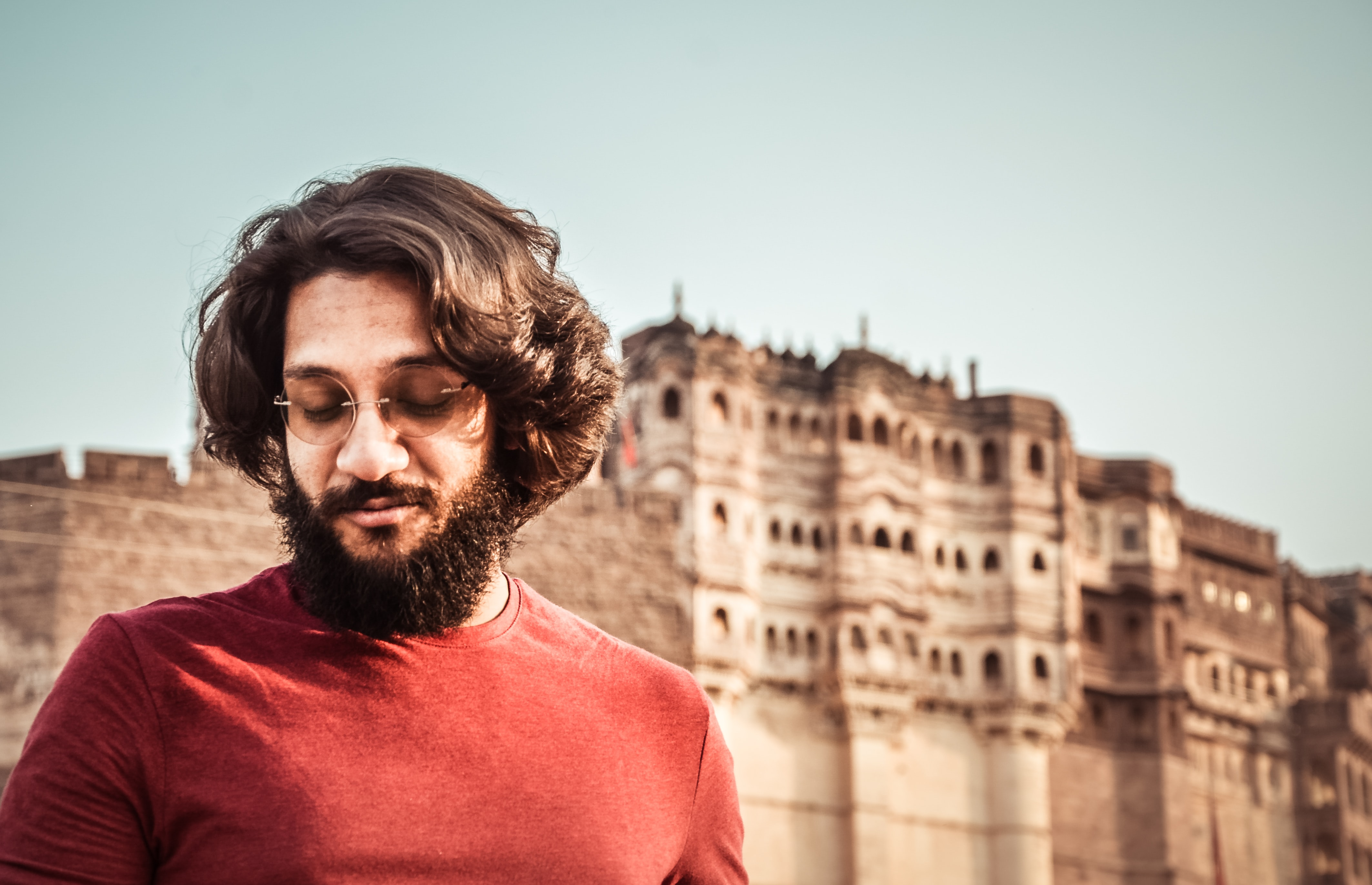 man wearing red crew-neck shirt standing near the ancient palace