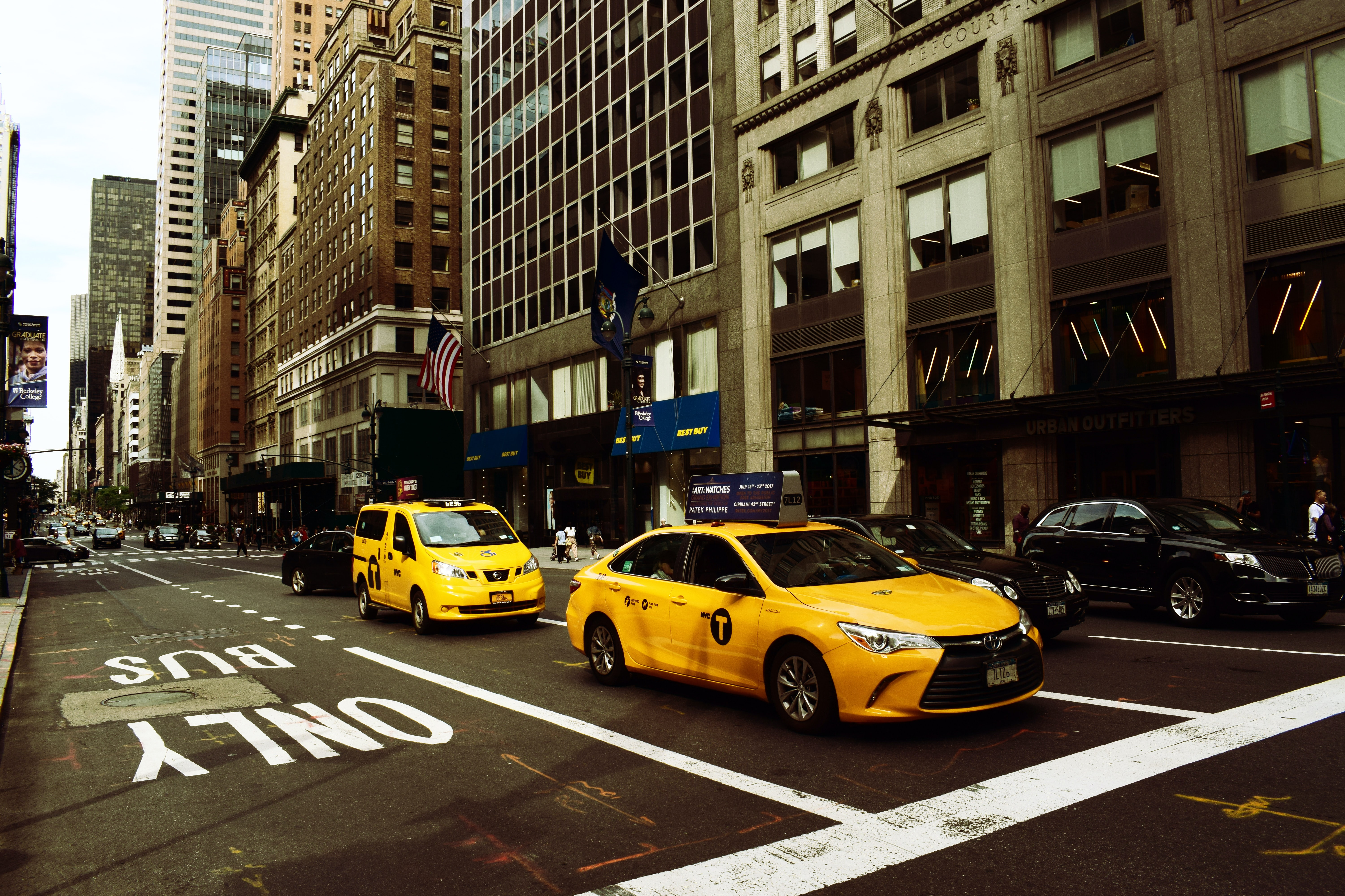 two yellow taxis on middle of road