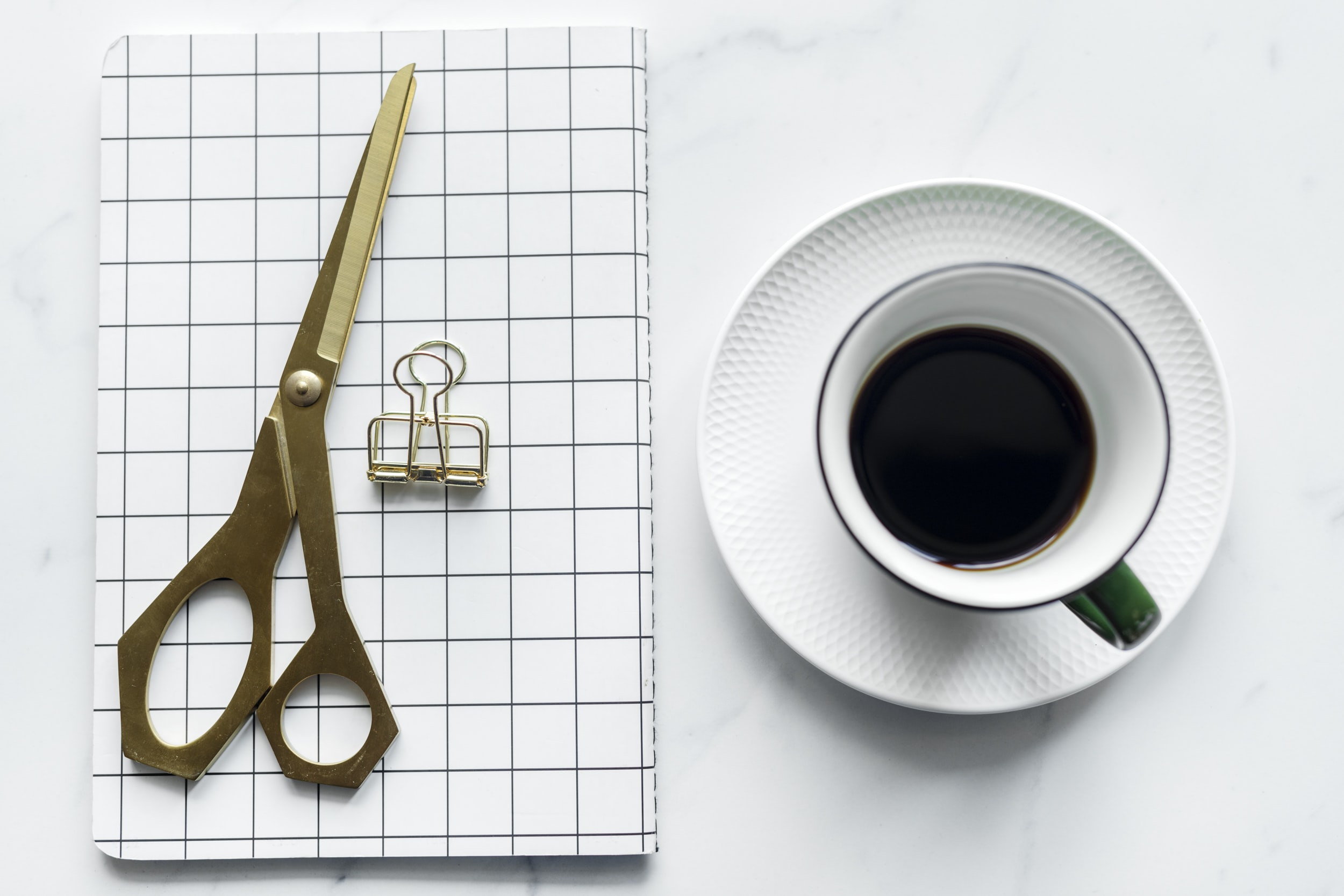 gold-colored scissors and white and green ceramic mug