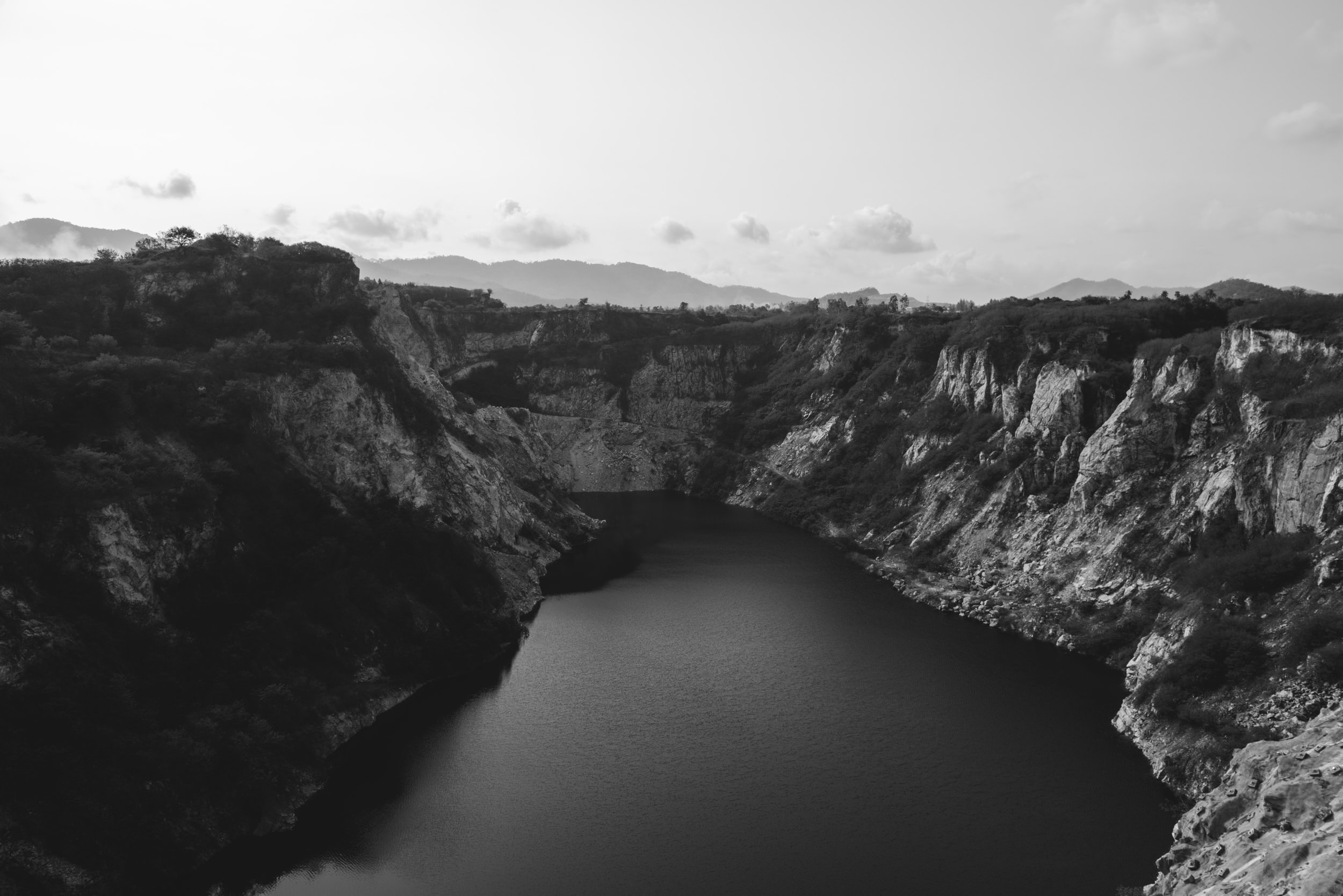 aerial grayscale photography of mountains near body of water