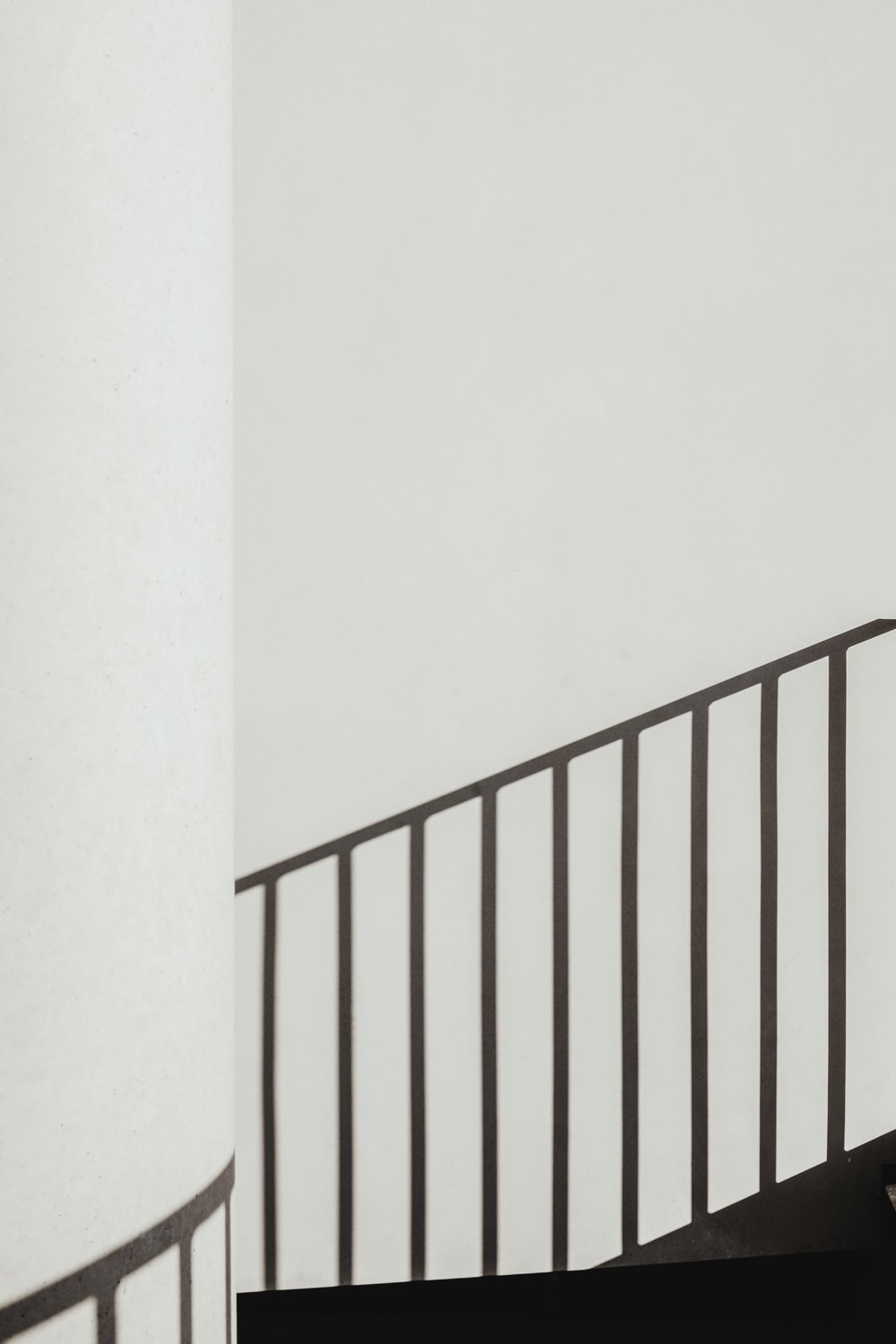 shadow of stair rails on white painted wall