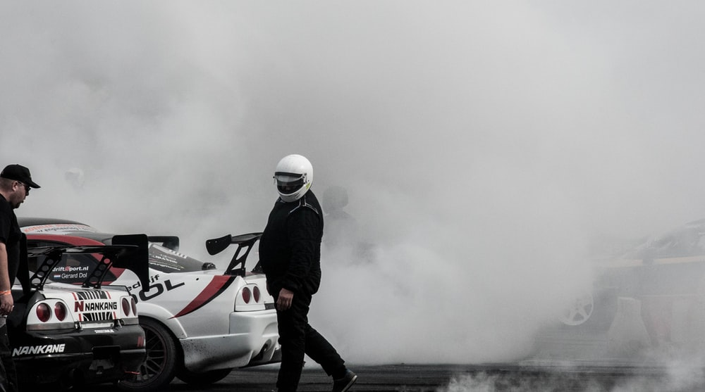 person standing beside racing cars