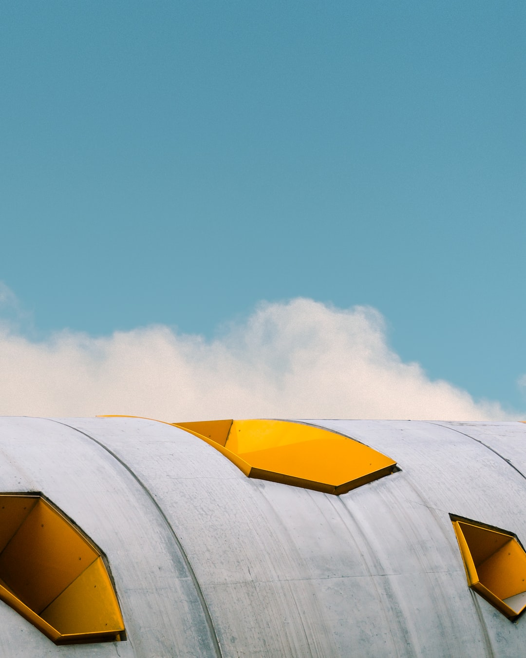 This photo is the remix of my own shot of this industrial concrete building and a sky captured by Samuel Zeller on Unsplash.