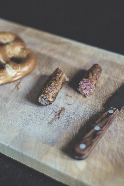 sliced sausage beside brown handle knife
